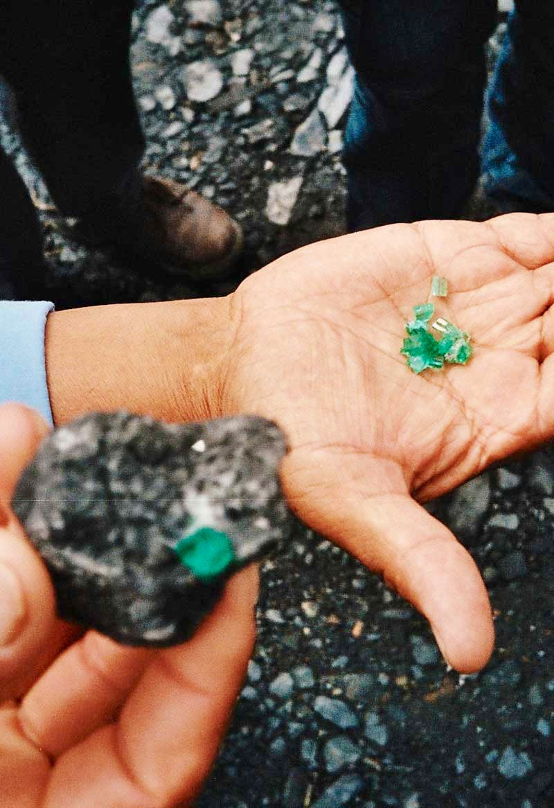 Raw emeralds in the hands of market traders in Colombia.