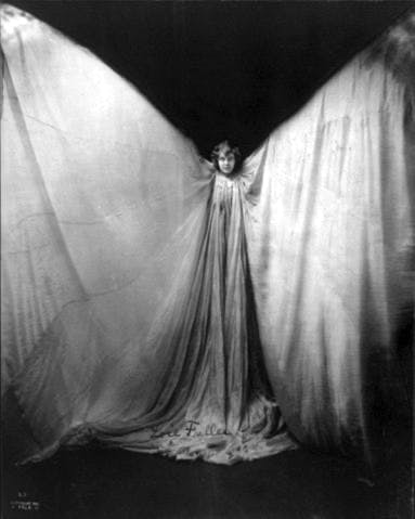 Loïe Fuller standing, facing front; wearing large gown, with arms raised in shape of a butterfly.