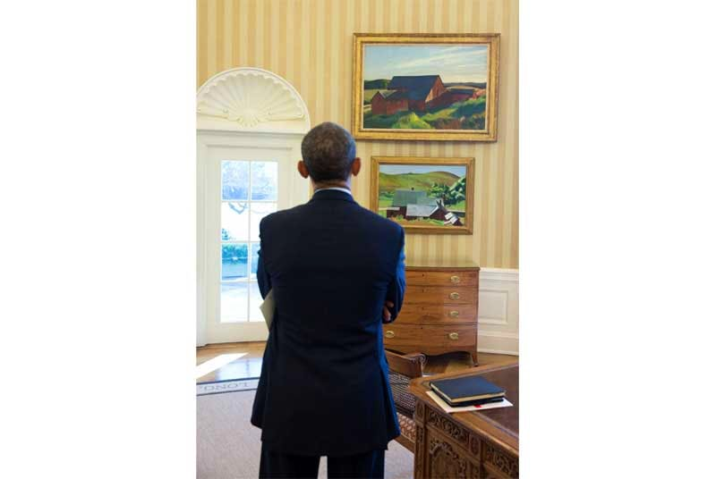 President Barack Obama looks at the Edward Hopper paintings now displayed in the Oval Office, February 7, 2014. The paintings are Cobb's Barns, South Truro, top, and Burly Cobb's House, South Truro