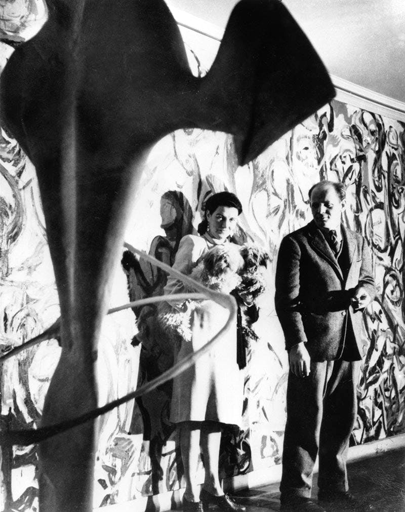 Peggy Guggenheim and Jackson Pollock in front of Pollock's Mural (1943) in the first-floor entrance hall of Guggenheim's residence, 155 East 61st Street, New York, c. 1946. Other work shown: unidentified David Hare sculpture (partially visible, foreground; c. 1946)