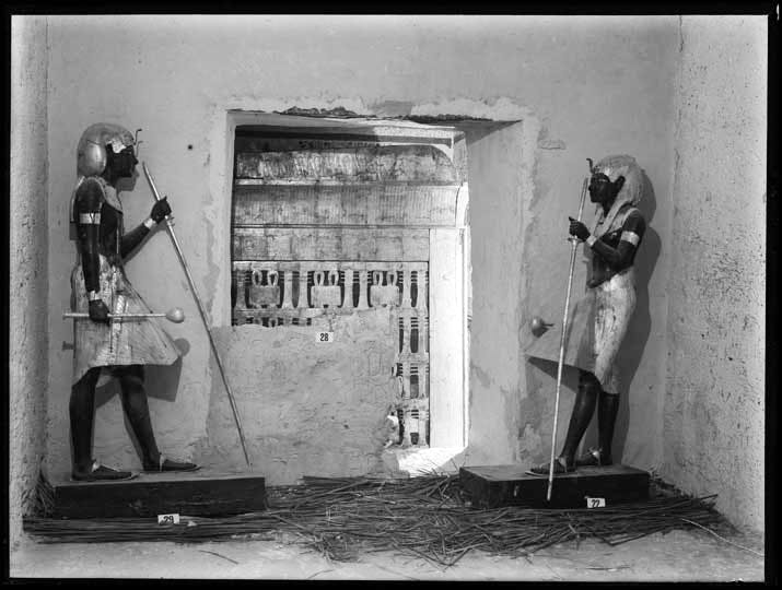 Two 'guardian' statues standing on either side of the entrance to the Burial Chamber. Photo by Harry Burton, 1922 © Griffith Institute, University of Oxford