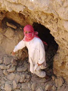 A looter points to where he found an object on an archaeological site in southern Iraq in 2003.