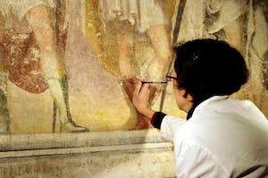 A restorer working on damaged frescos in the crypt of Sant'Eustorgio church at Milan, Italy.