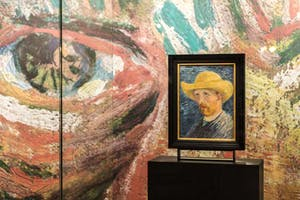 Vincent Van Gogh's 'Self-Portrait with Straw Hat' (1887) against an enlarged detail of the eyes from 'Self-Portrait with Grey Felt Hat (1887) on the ground floor of the Van Gogh Museum
