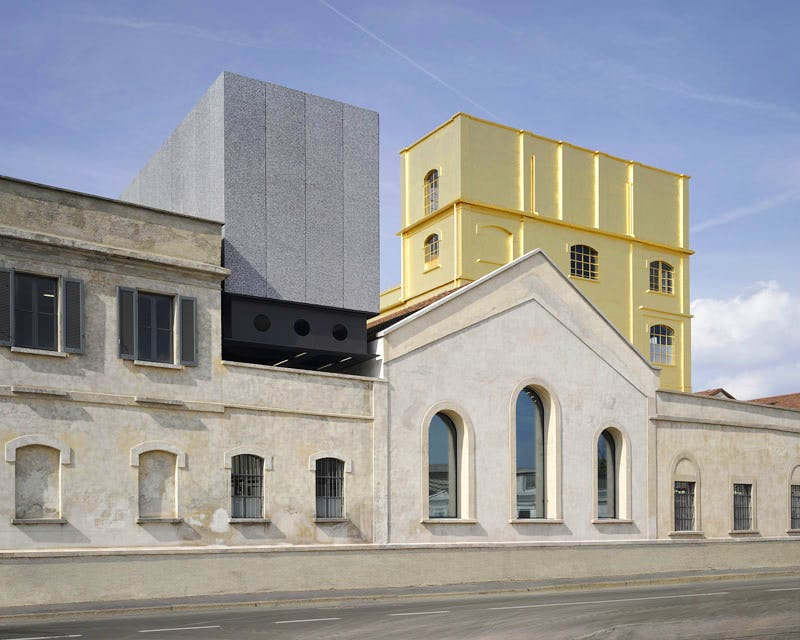 Exterior view of the Fondazione Prada in Milan, designed by Rem Koolhaas and OMA, showing a pre-existing tower covered in 24-carat gold leaf.