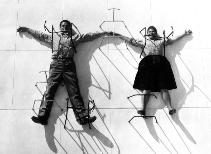 Charles and Ray Eames posing with chair bases