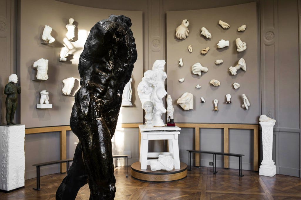 Installation view showing Rodin's The Walking Man (1907) with pieces from the sculptor's collection of antiquities