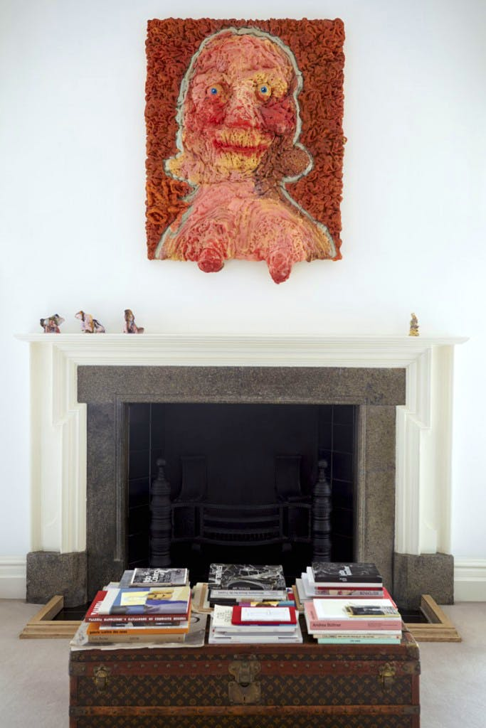 Saggy Titties (2007) by Nicole Eisenman hangs above a fireplace