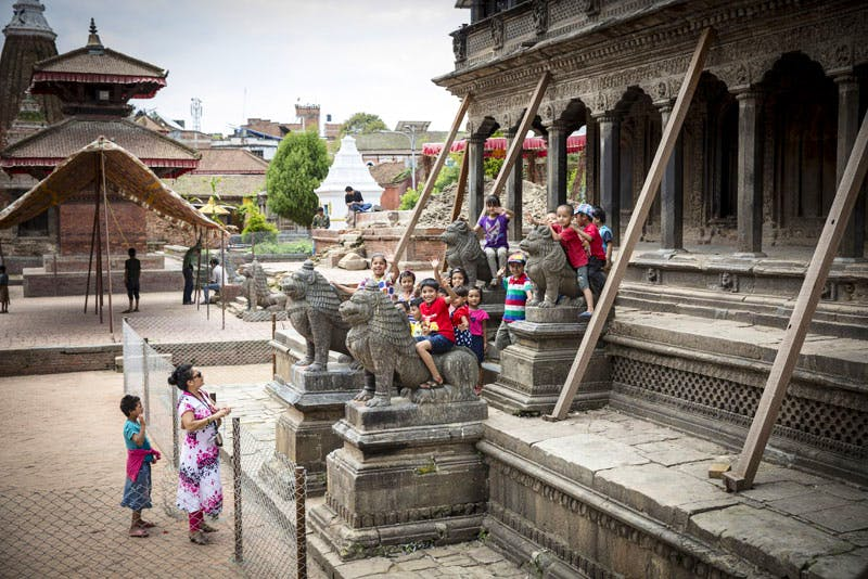 Children play on the stone lions at the base of the Khrishna Mandir, which was shored up after the 2015 earthquake and awaits restoration by the KVPT. Photo: Scott Newman