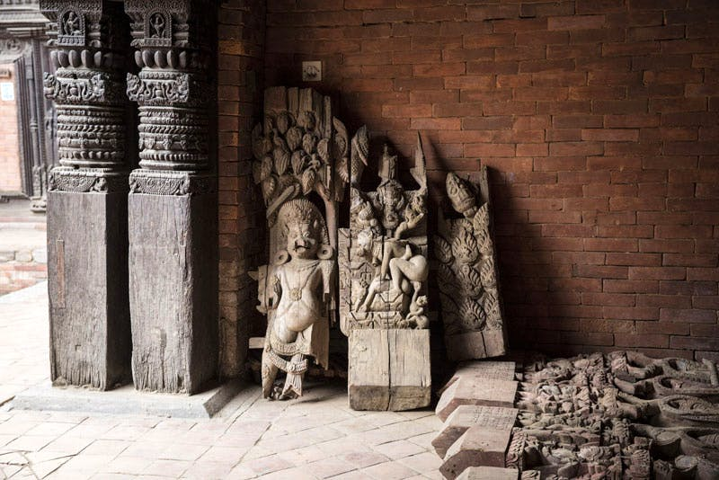 Architectural fragments rescued from the debris of a fallen temple in Patan Darbar Square are sheltered in a palace courtyard, now part of the Patan Museum, awaiting conservation and reuse. May 2015. Photo: Scott Newman