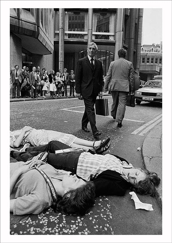 Greenham Common protesters stage a Die-in outside the Stock Exchange during the morning rush hour as U.S. President Reagan arrives in Britain, City of London (1982), Edward Barber