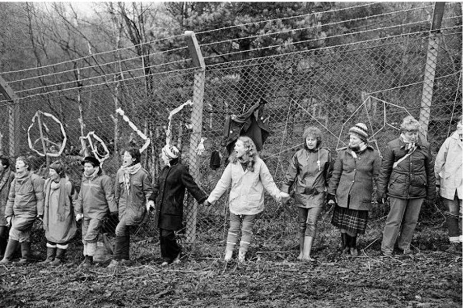 'Embrace the Base': 30,000 women link hands, completely surrounding the nine mile perimeter fence at RAF/USAF Greenham Common, Berkshire (1982), Edward Barber.