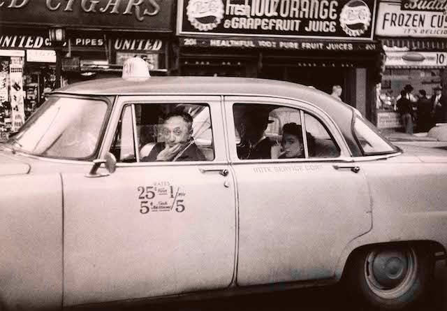Taxicab driver at the wheel with two passengers, N.Y.C