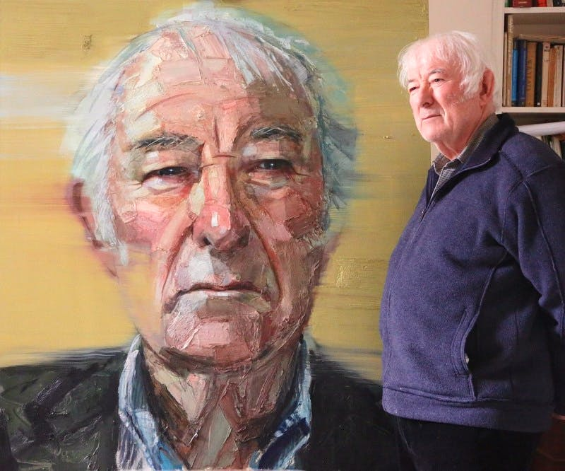 Seamus Heaney (1939–2013) poses with his portrait by Colin Davidson.