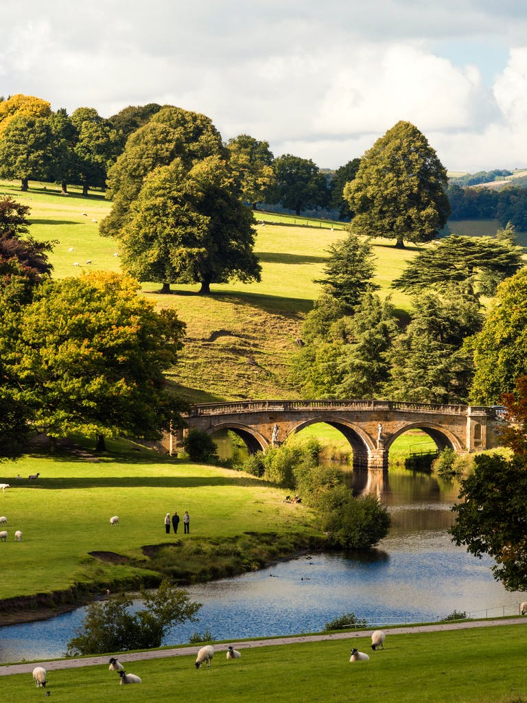 View over the parkland at Chatsworth House, and the River Derwent and stone bridge.