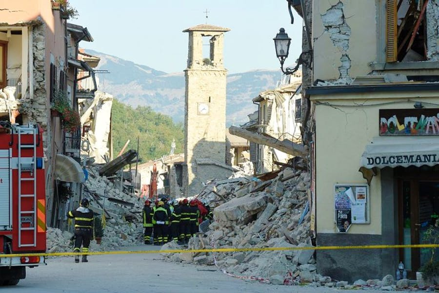 Firefighters gather near the damaged Sant'Agostino church in the central Italian village of Amatrice on 26 August, 2016, three days after a 6.2-magnitude earthquake struck the region. ANDREAS SOLARO/AFP/Getty Images