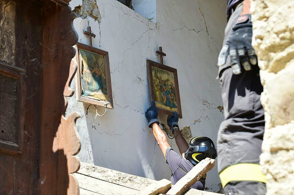 Firefighters recover a religious painting from a damaged church in the village of Rio, some 10 kms from the central Italian village of Amatrice, on August 28, 2016. ALBERTO PIZZOLI/AFP/Getty Images