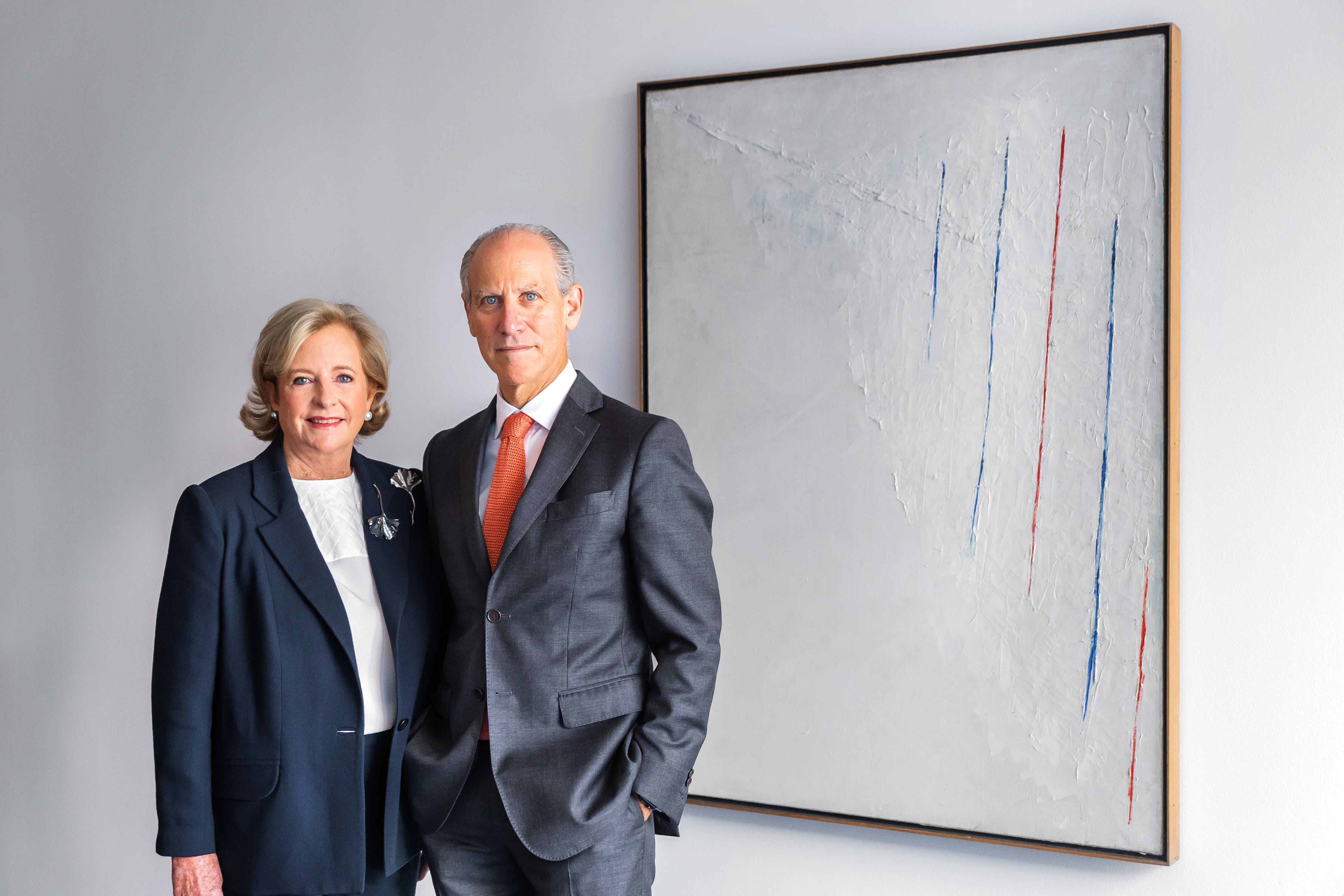 Patricia Phelps de Cisneros and Glenn D. Lowry, Director, The Museum of Modern Art, stand next to Alejandro Otero, 'Colored Lines on White Background' (1950) © 2016 Scott Rudd