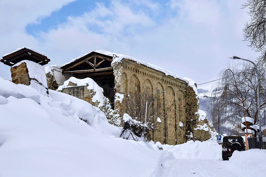 Italian military vehicles stand guard in front a Sant'Agostino church in Amatrice on January 19, 2017 after a 5.7-magnitude earthquake struck the region. The church was severely damaged in a major quake in August 2016. ANDREAS SOLARO/AFP/Getty Images