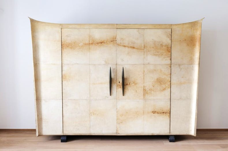Vellum cabinet with black wood handles, made by Valzania.