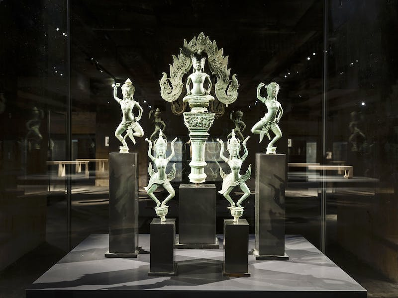 Set of bronzes representing Apsaras and a sitting deity, 12th century, Angkor Wat, installation view, Feuerle Collection, Berlin.. Photo: Thomas Meyer