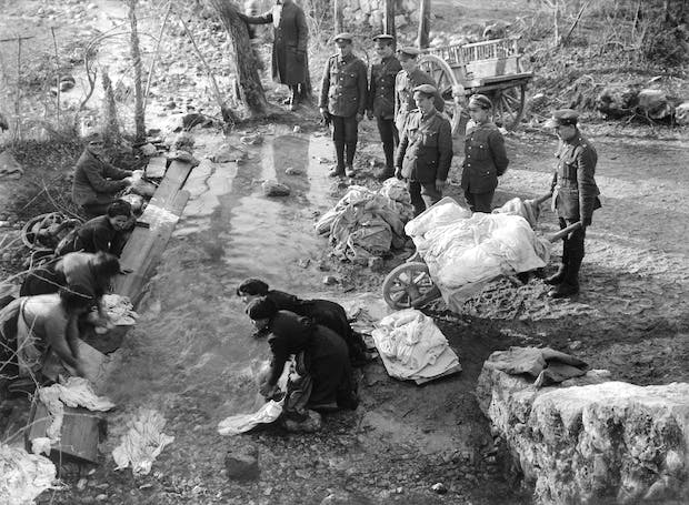 Men of the Royal Engineers watch as their clothes are washed in a stream by Italian peasant women (November-December 1917), Ernest Brooks. Courtesy: Imperial War Museum
