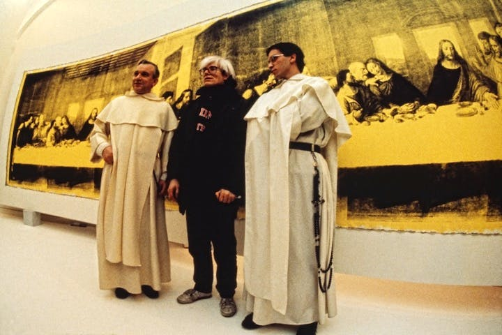 Andy Warhol in front of The Last Supper (Yellow) (1986) at the opening of Andy Warhol – Il Cenacolo at Palazzo delle Stelline, Milan, January 22, 1987. © Archivio Garghetti. Courtesy Gagosian.