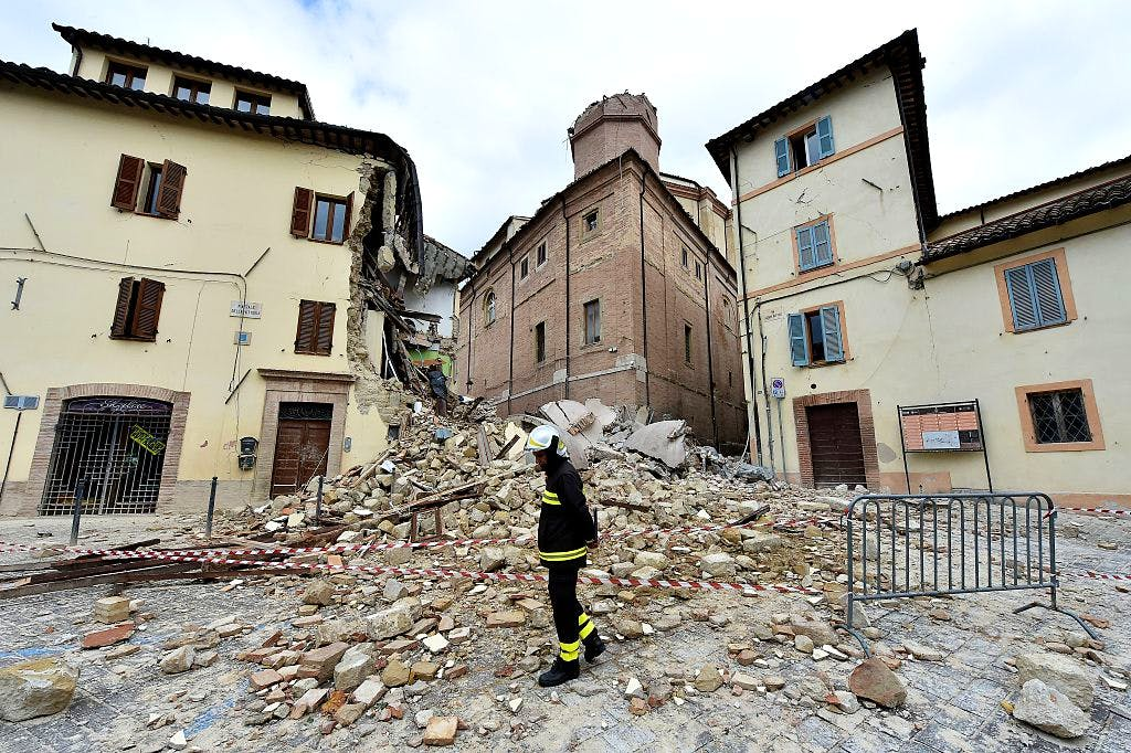 A firefighter stands in front of the collapsed bell tower of the Santa Maria in Via church in the 'red zone', an area cordoned off for safety reasons, in Camerino, where 80 per cent of the houses have been left uninhabitable after two earthquakes hit the region. (28 October, 2016) ALBERTO PIZZOLI/AFP/Getty Images