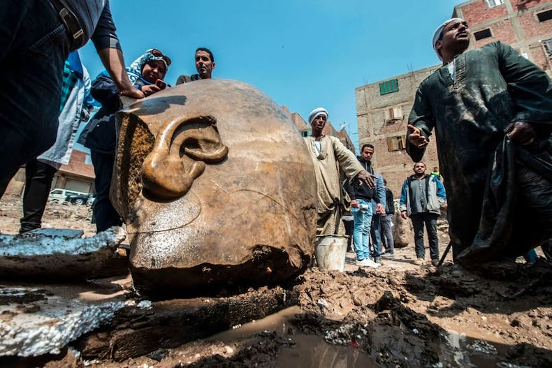 Egyptian workers look at the site of a new discovery by a team of German-Egyptian archeologists in Cairo's Mattarya district on March 9, 2017.