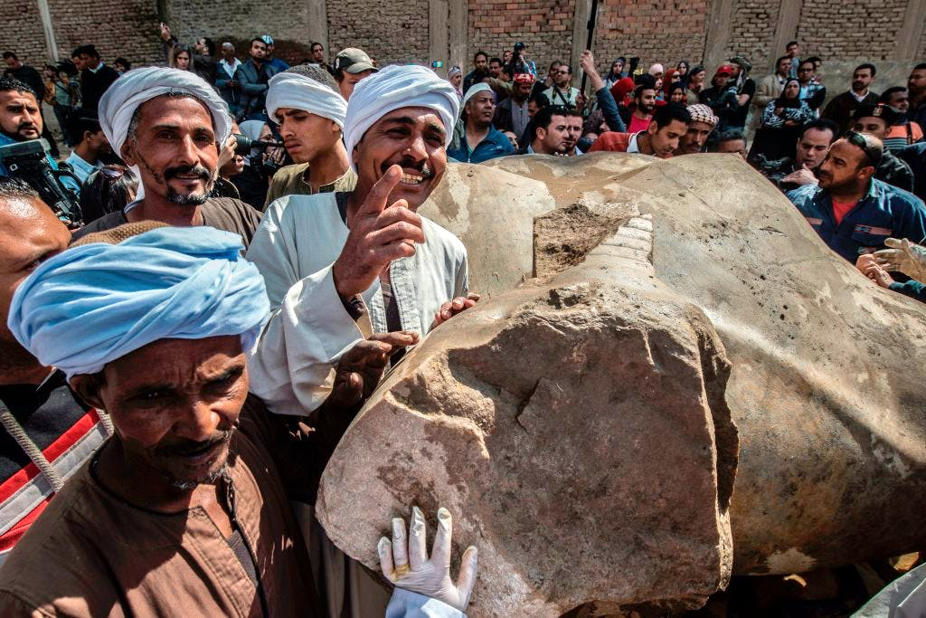 Egyptian workers pose next to an excavated statue, recently discovered by a team of German-Egyptian archeologists, in Cairo's Mattarya district on March 13, 2017.