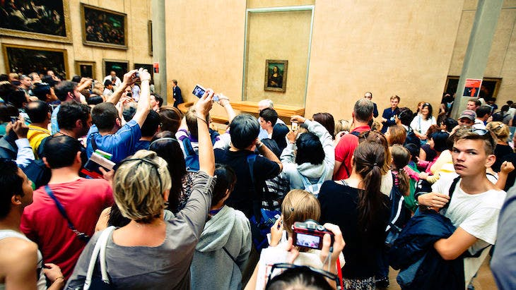 Crowds taking photos of the Mona Lisa in the Louvre. Photo: Wikimedia commons