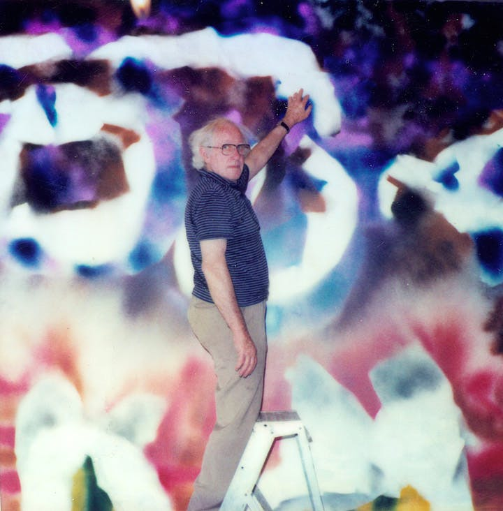 Sidney Nolan pictured with his work Abstract (1986). Courtesy of the Sidney Nolan Trust