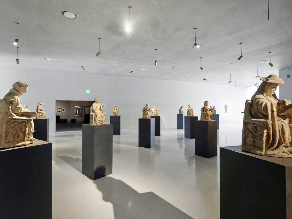 14th-century stone figures from the archivolt of the St Peter Portal, Cologne Cathedral, displayed in a gallery at Kolumba