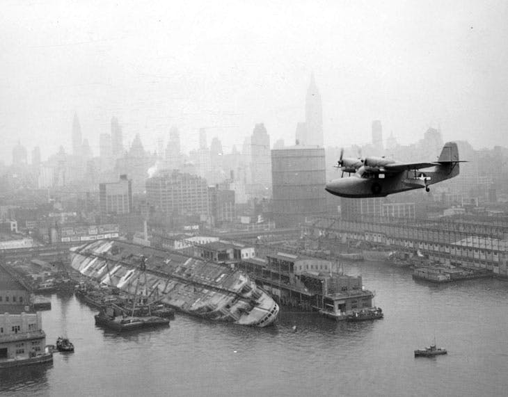A U.S. Coast Guard Grumman J4F Widgeon flies over the wreckage of the USS Lafayette (AP-53) at Pier 88, New York harbor, on 12 August 1943