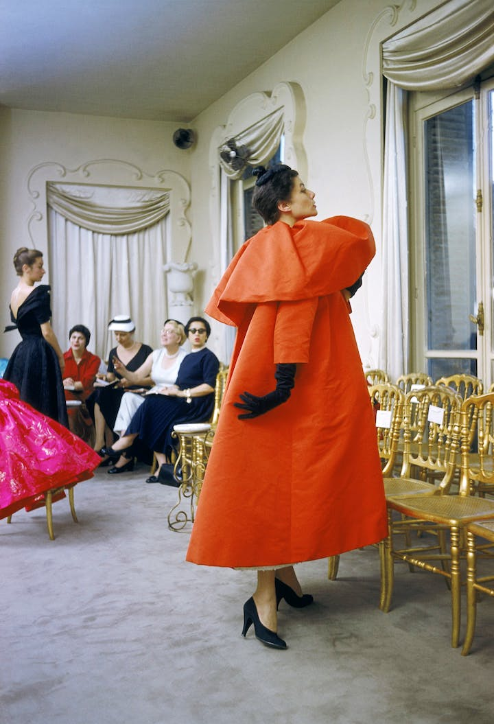 Model wearing Balenciaga orange coat as I. Magnin buyers inspect a dinner outfit in the background in Paris, 1954. © Mark Shaw / mptvimages.com