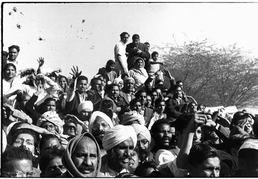 Gandhi's funeral. Crowds gathered between Birla House and the cremation ground, throwing flowers (1948), Henri Cartier-Bresson. © Henri Cartier-Bresson/Magnum Photos