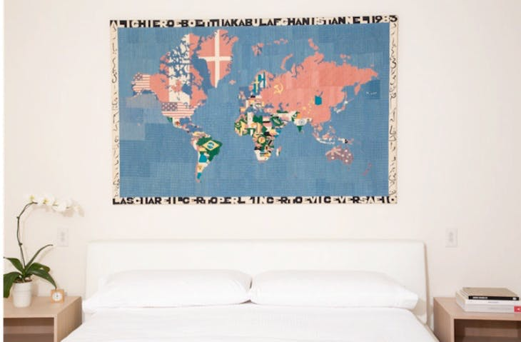 Lasciare il certo per l'incerto e viceversa (1983) by Alighiero Boetti hangs on a bedroom wall