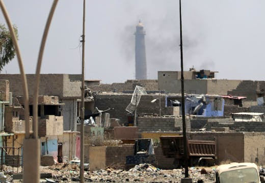 A general view shows smoke rising near the leaning Al-Hadba minaret in the Al-Nuri mosque compound, as Iraqi government forces advance in western Mosul's Zanjili neighbourhood on 7 June, 2017, during ongoing battles against Islamic State (IS) group fighters. Photo: KARIM SAHIB/AFP/Getty Images