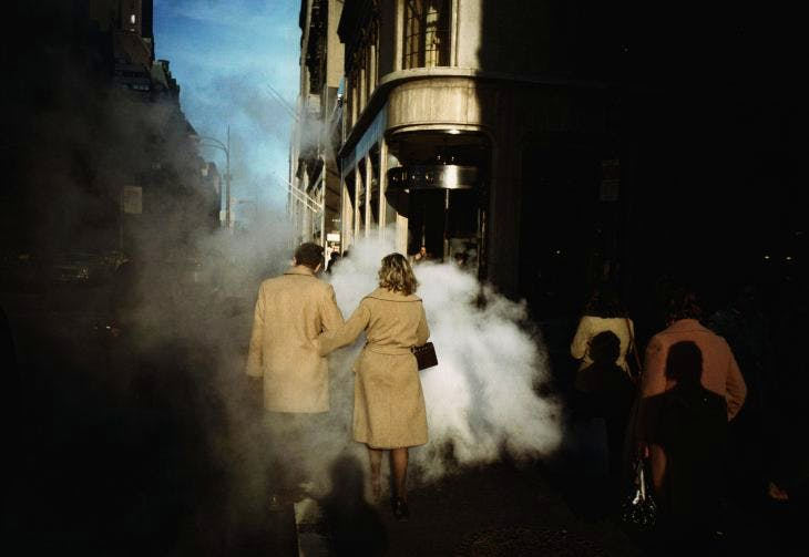 Camel Coat Couple in Street Steam, New York City, 1975, Joel Meyerowitz. Courtesy of the artist and Howard Greenberg Gallery.
