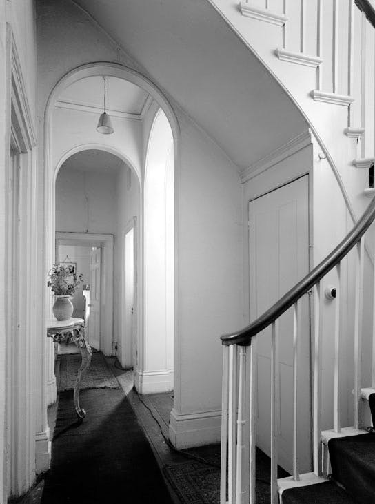 The interior of Sandycombe Lodge before restoration, showing the curved staircase and arched corridor. © Country Life