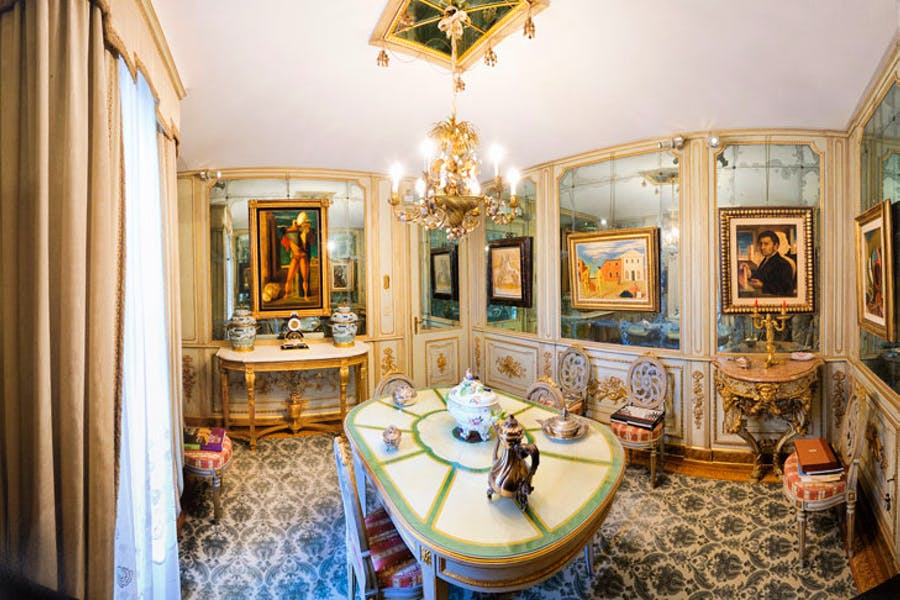Paintings by De Chirico hang in the mirrored dining room of Francesco Federico Cerruti's villa. Photo: Gabriele Gaidano