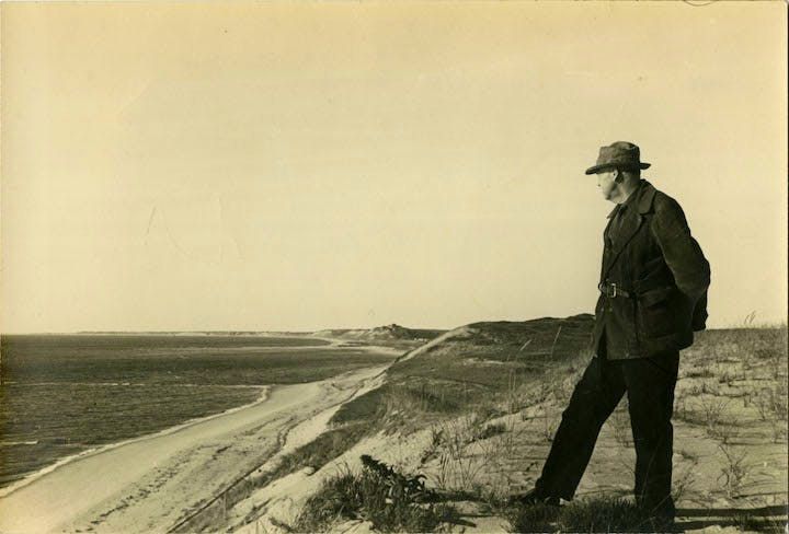 Portrait of Edward Hopper in the sand dunes of Cape Cod, c. 1930-1940. The Sanborn Hopper Archive at the Whitney Museum of American Art