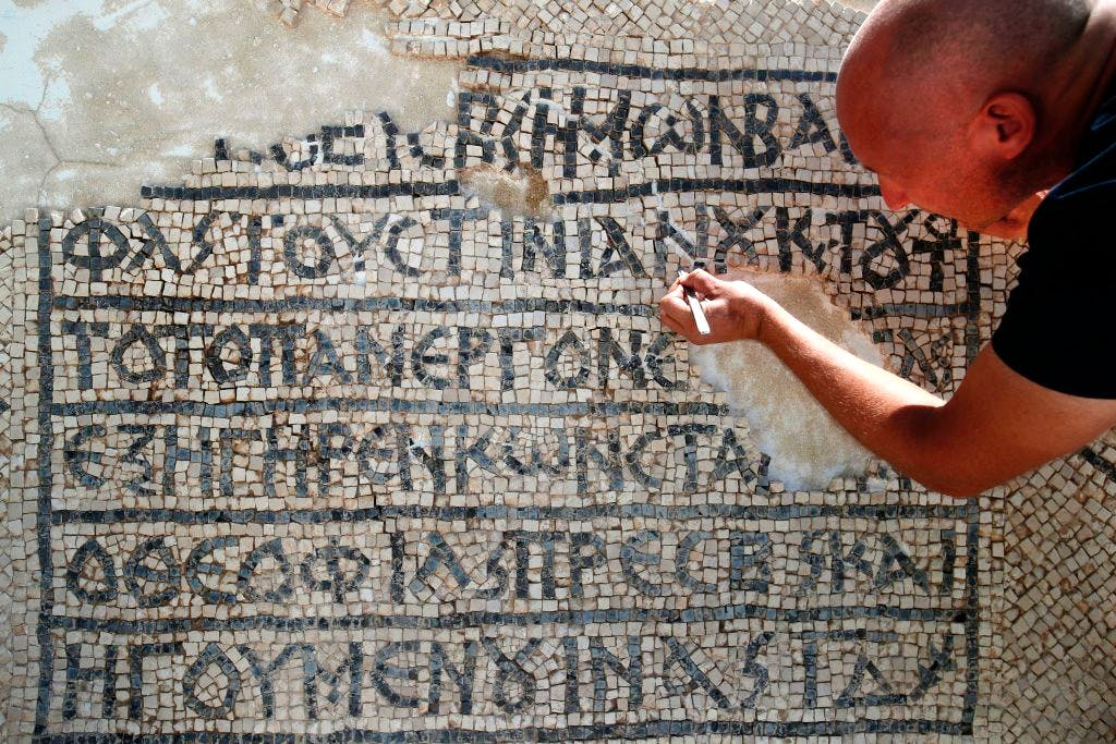 An archaeologist works on part of a 1,500-year-old mosaic discovered near Jerusalem's Damascus Gate, on 23 August 2017. AHMAD GHARABLI/AFP/Getty Images