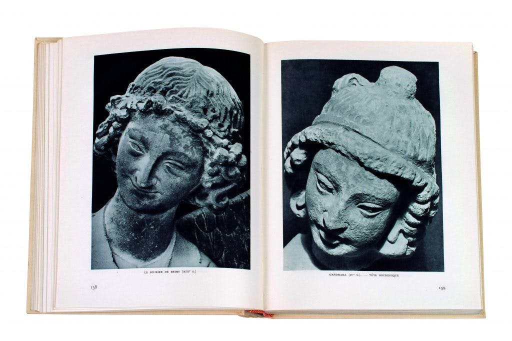 A spread from Les voix du siècle (1953) showing the 13th-century Le Sourire de Reims (verso) and a 4th-century Gandharan head from Afghanistan (recto). photo: Stephan Vavra