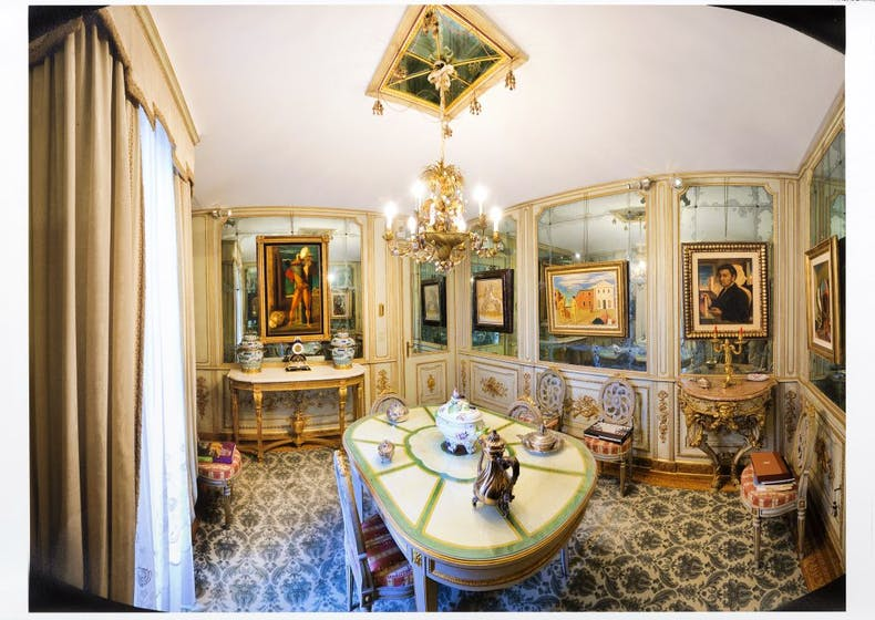 Painting by De Chirico hang in the mirrored dining room of the Cerruti villa