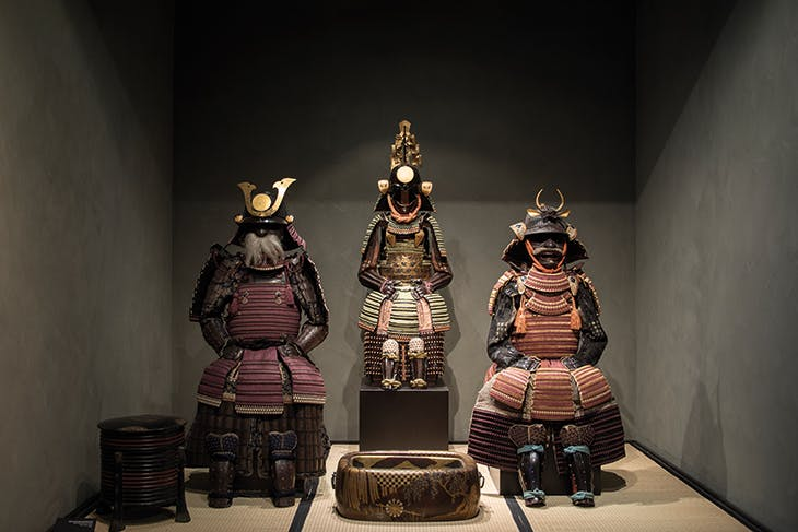 An open display platform in the museum, with a tachido tosei gusoku armour signed by Joshu Ju Saoteme letada and dated 1702 to the right of a boy's armour from the 18th century (centre).