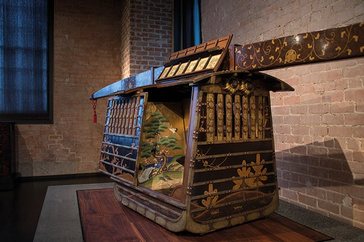 A 19th-century norimono or palanquin in the Ann & Gabriel Barbier-Mueller Museum, bearing the crest of the Tokugawa clan and decorated with trees and plants symbolising resilience and perseverance.