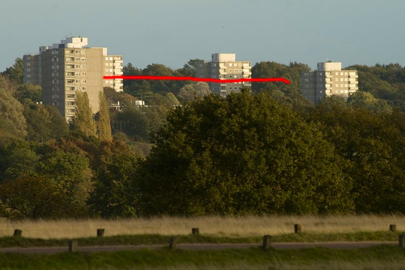 The Alton Estate seen from Richmond Park. The red line indicates the eighth floor of the current blocks on the site, the upper number of storeys proposed for the new buildings to replace blocks like those only just visible below it through the trees.