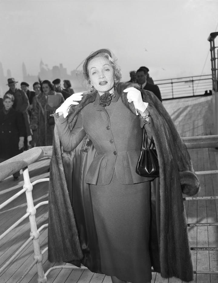 Photograph of Marlene Dietrich wearing a day suit by Christian Dior on-board the Queen Elizabeth arriving in New York, 21 December 1950. © Getty Images