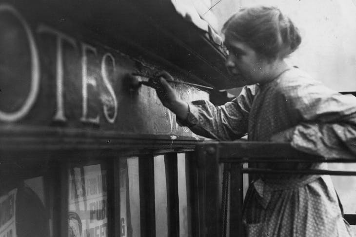Sylvia Pankhurst painting onto the façade of the Women's Social Defence League shop in Bow Street, London (11 October 1912).